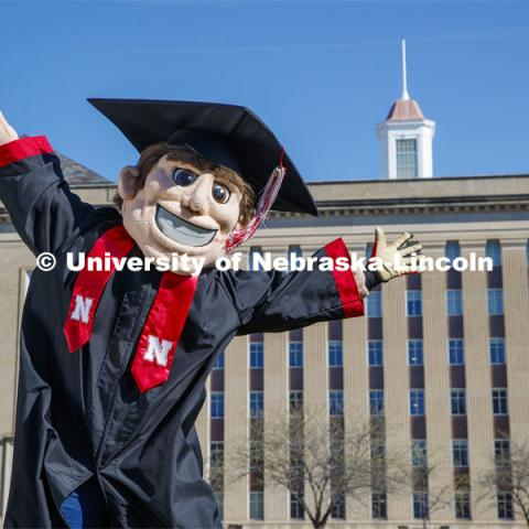 Herbie Husker leaps for joy on the lawn in front of Love Library and is decked out in graduation attire for the Spring Commencement that was which streamed online and aired on NET because of the COVID-19 pandemic. April 10, 2020. Photo by Craig Chandler / University Communication.