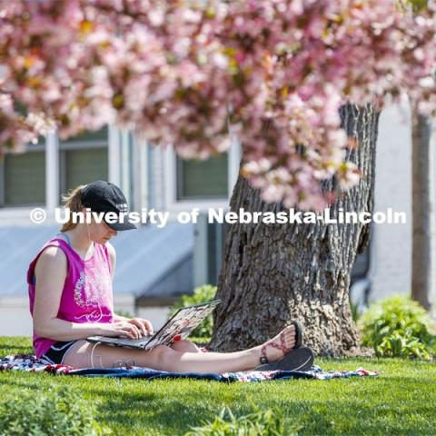 Kelsey Eihausen, sophomore from Bennington, studies outside of the Phi Mu sorority. She and other members staying in the chapter house study outside on a spring day. April 28, 2020. Photo by Craig Chandler / University Communication.