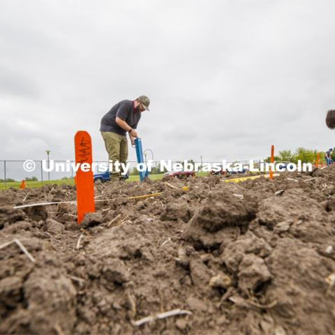 James Schnable operates a hand planter in the freshly tilled soil as Leighton Wheeler, May graduate in biochemistry, places seed packets next to row markers for the next section of planting. East Campus ag fields. May 20, 2020. Photo by Craig Chandler / University Communication.