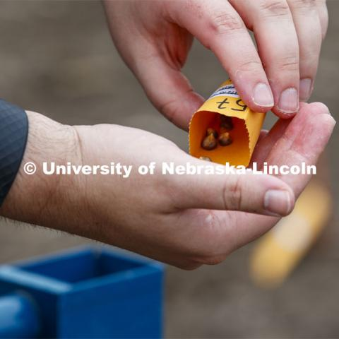 James Schnable pours corn kernels into his hand for the next row of planting. East Campus ag fields. May 20, 2020. Photo by Craig Chandler / University Communication.