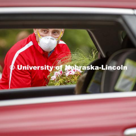 Stacy Adams, Associate Professor of Practice for Agronomy and Horticulture, waits for a driver to unlock the rear hatch so he can set a flat of flowers in the SUV. The University of Nebraska-Lincoln Horticulture Club hosted its first-ever plant giveaway Thursday, a replacement for the club's annual plant sale and fundraiser was due to the university shutdown in response to the global pandemic in mid-March. A prepackaged assortment of plants in a cardboard flat will be ready for each recipient. There were two sessions of giveaways with 100 flats of plants at each one. It only took 22 minutes to give away the morning allocation of flats. May 21, 2020. Photo by Craig Chandler / University Communication.
