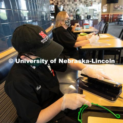 Dinning Services employees, Rochan Pinho, Janet Nichols and Dami Olsen, assemble face shields at Harper Dining Center. Once school starts up, they will use the shields for prevention of the spread of COVID-19. April 28, 2020. Photo by Gregory Nathan / University Communication.
