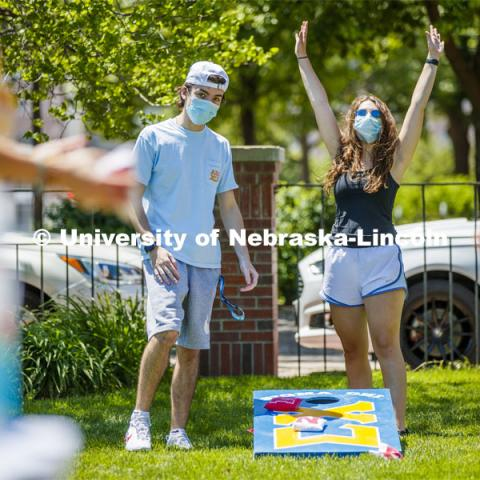 Soffi Olson celebrates her teammates throw as Kaleb Brady watches during a corn hole game at Sigma Chi recruitment day. Sigma Chi members are wearing masks as a result of the COVID-19 pandemic. May 29, 2020. Photo by Craig Chandler / University Communication.