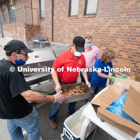 University Assistant professor Benny Mote hands a pan of grilled pork burgers to a worker at the Lincoln City Mission. The pork, donated by pig farmer and University of Nebraska–Lincoln animal science alumnus, Bill Luckey, was the result of generosity, ingenuity, collaboration and a spirit of Nebraskans helping Nebraskans among the state's pork producers, the Food Bank of Lincoln and the University of Nebraska–Lincoln. June 18, 2020. Photo by Gregory Nathan / University Communication. June 18, 2020. Photo by Gregory Nathan / University Communication.