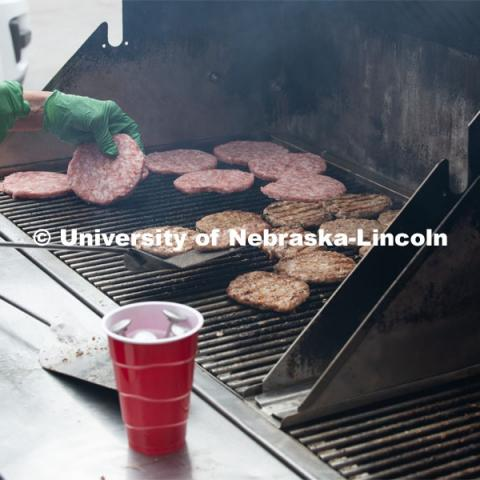 A grill full of pork burgers gets cooked up for the Lincoln City Mission. The pork, donated by pig farmer and University of Nebraska–Lincoln animal science alumnus, Bill Luckey, was the result of generosity, ingenuity, collaboration and a spirit of Nebraskans helping Nebraskans among the state's pork producers, the Food Bank of Lincoln and the University of Nebraska–Lincoln. June 18, 2020. Photo by Gregory Nathan / University Communication.