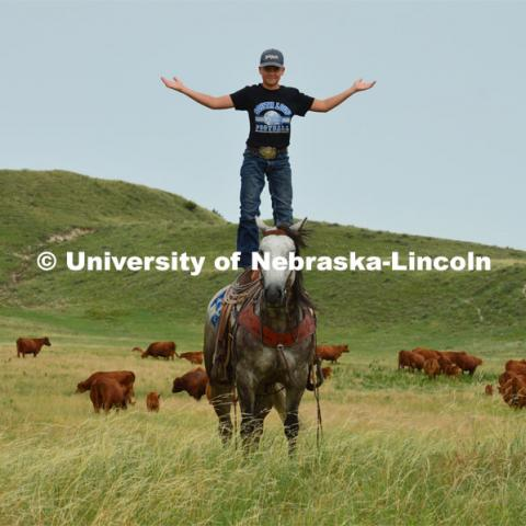 A young rancher shows his skills of standing on the back of his horse. Cattle and livestock on the Diamond Bar Ranch north of Stapleton, NE, in the Nebraska Sandhills. June 23, 2020. Photo by Natalie Jones.  Photos are for UNL use only.  Any outside use must be approved by the photographer.