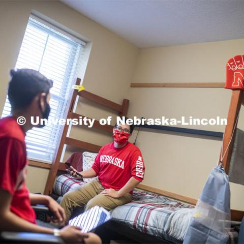 PJ Miguelino talks with Edwin Mendez-Rodriguez in a University Suites Residence Hall room. Photo shoot of students wearing masks and practicing social distancing. June 24, 2020. Photo by Craig Chandler / University Communication.