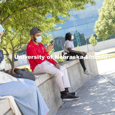 Aldi Airori checks his phone while wearing a mask and practicing social distancing outdoors. Photo shoot of students wearing masks and practicing social distancing. June 24, 2020. Photo by Craig Chandler / University Communication.