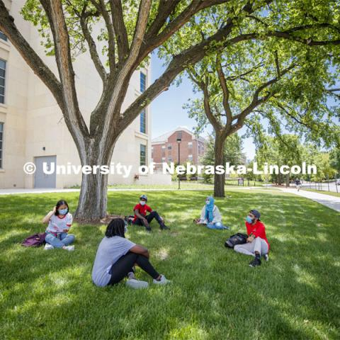 A group of students wearing masks and practice social distancing hangout under a tree on City Campus. Photo shoot of students wearing masks and practicing social distancing. June 24, 2020. Photo by Craig Chandler / University Communication