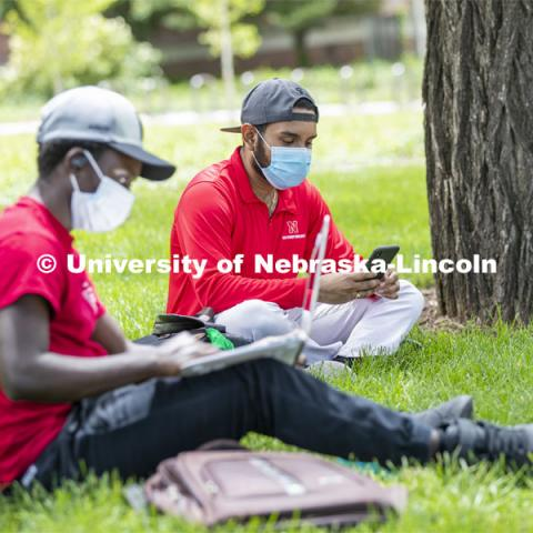 Mark Iradukunda works on his laptop and Aldi Airori checks his phone while wearing masks and practicing social distancing outdoors. Photo shoot of students wearing masks and practicing social distancing. June 24, 2020. Photo by Craig Chandler / University Communication.
