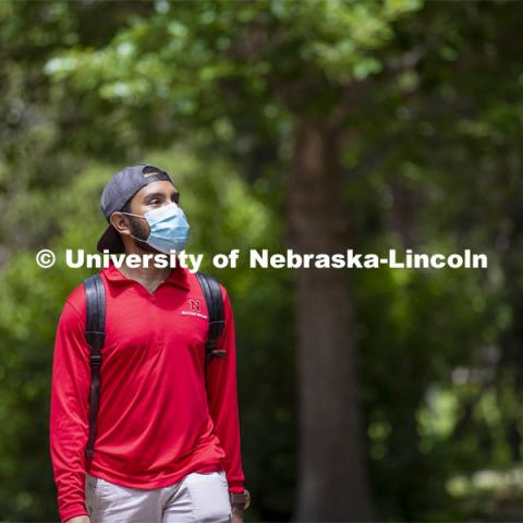 Aldi Airori walks across campus wearing his mask. Photo shoot of students wearing masks and practicing social distancing. June 24, 2020. Photo by Craig Chandler / University Communication.