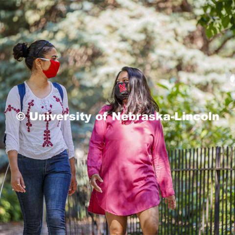 Asmita Jayswal, junior in computer science, and Esha Mishra, graduate student in physics, walk along R Street wearing the new N mask. More than 60,000 face masks are to be distributed to all students, faculty and staff for the fall semester. June 26, 2020. Photo by Craig Chandler / University Communication.
