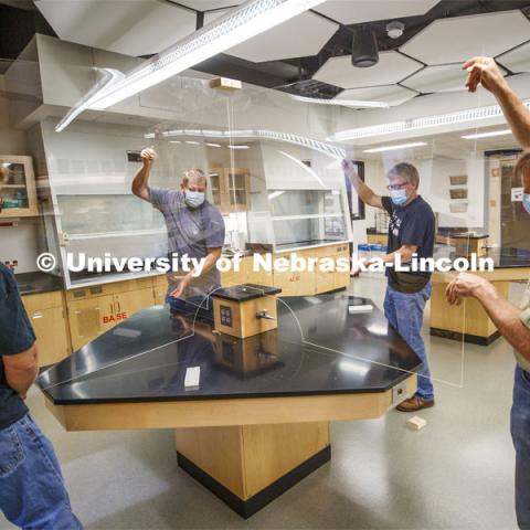 Nebraska's (from left) Mark Thompson, Keith Placek, Jody Redepenning and Pat Pribil lift an acrylic barrier onto a lab table in Hamilton Hall. The barrier is a prototype that is being refined as part of the university's preparations for a return to on-campus instruction for the fall semester. The barriers will allow chemistry lab tables to be divided into four sections. The barrier is the second prototype and will be refined as part of 78 barriers being manufactured for the beginning of fall classes. Redepenning is chair and professor of chemistry. Thompson, Placek and Pribil are part of the university's Chemistry/Physics and Astronomy Instrument Shop. July 1, 2020. Photo by Craig Chandler / University Communication.