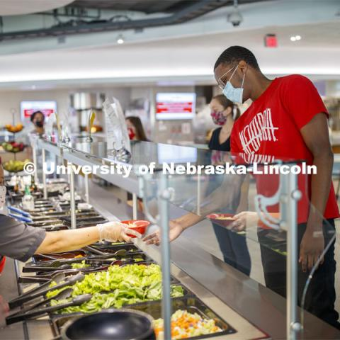 Students selecting food and being served by UNL Dining Staff. Photo shoot of students wearing masks and practicing social distancing in dining services in Willa Cather Dining Center. July 1, 2020. Photo by Craig Chandler / University Communication.