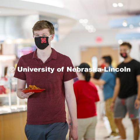 Young man wearing a Husker mask. Photo shoot of students wearing masks and practicing social distancing in dining services in Willa Cather Dining Center. July 1, 2020. Photo by Craig Chandler / University Communication.