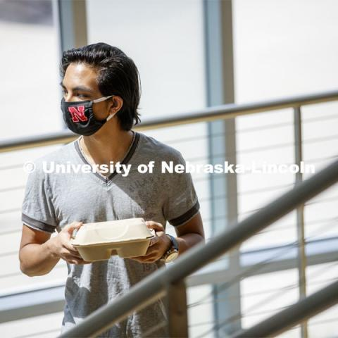 A young man wearing a Husker mask gets takeout dining from the Willa Cather Dining Center. Photo shoot of students wearing masks and practicing social distancing in dining services in Willa Cather Dining Center. July 1, 2020. Photo by Craig Chandler / University Communication.