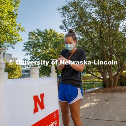 Maggie Ferguson, a May 2020 College of Business graduate, tries out a hand sanitizer station outside Westbrook Music Building. It is one of the more than 1,500 new hand sanitizer stations being distributed around the three UNL campuses. July 28, 2020. Photo by Craig Chandler / University Communication.