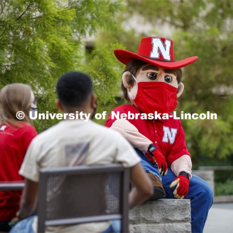 Photo shoot of students with Herbie on city campus display mask wearing, social distancing. Students sitting at tables and hanging out with Herbie Husker. August 5, 2020. Photo by Craig Chandler / University Communication.