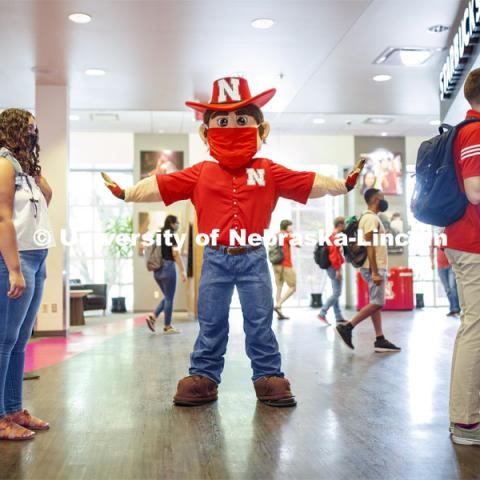 Photo shoot of students with Herbie on city campus display mask wearing, social distancing. Students stand in line to get coffee from Starbucks at the Nebraska Union. Herbie makes sure everyone is social distancing. August 5, 2020. Photo by Craig Chandler / University Communication.