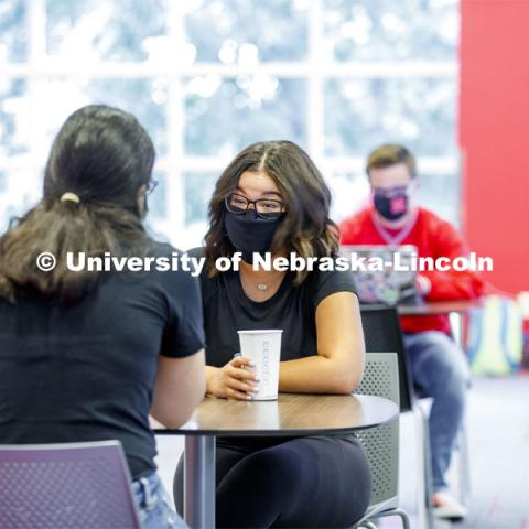 Photo shoot of students on city campus display mask wearing, social distancing. Students wearing masks while sitting together in the Nebraska Union. August 5, 2020. Photo by Craig Chandler / University Communication.