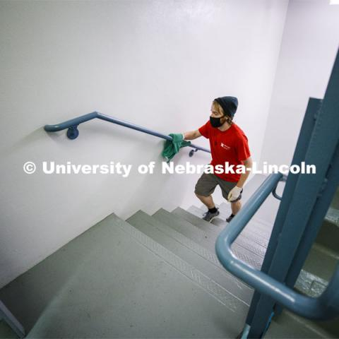 Kenny Shuman, a housing student worker, wipes down the stairway railings to keep move in clean. First day of residence hall move in. August 13, 2020. Photo by Craig Chandler / University Communication.