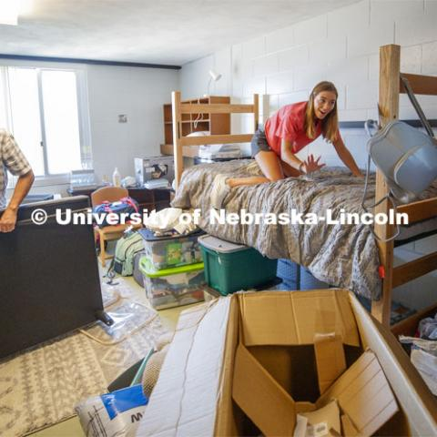 Kailey Trampe of Axtell, NE, smiles for her mom, Sara, as she makes her bed. Kailey's dad, Todd, works on assembling the futon. First day of residence hall move in. August 13, 2020. Photo by Craig Chandler / University Communication.