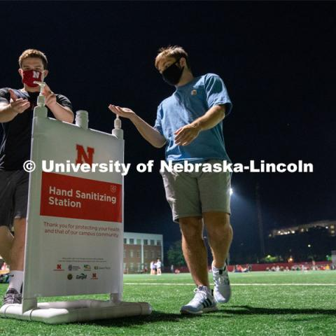 Two students make use of a hand sanitizing station while leaving Mabel Lee Fields at the conclusion of the HuskerMania Masker Singer event. August 21, 2020. Photo by Jordan Opp for University Communication.