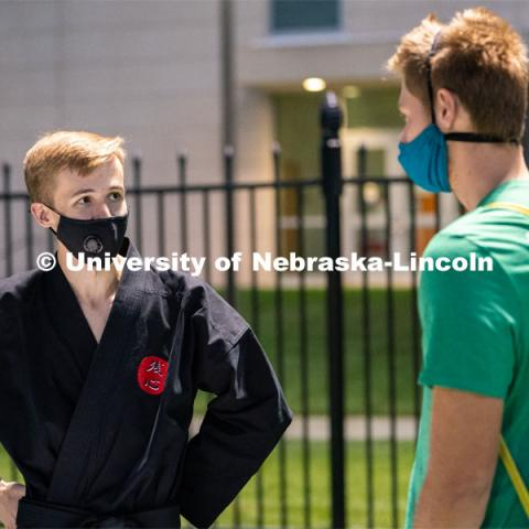 A member of the Nebraska Judo Club speaks to a student during the HuskerMania Masker Singer event at Mabel Lee Fields. August 21, 2020. Photo by Jordan Opp for University Communication.