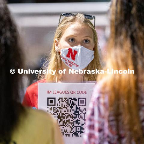 An employee of Nebraska Campus Recreation (center) speaks to students and holds up a QR code for them to scan during the HuskerMania Masker Singer event at Mabel Lee Fields. August 21, 2020. Photo by Jordan Opp for University Communication.