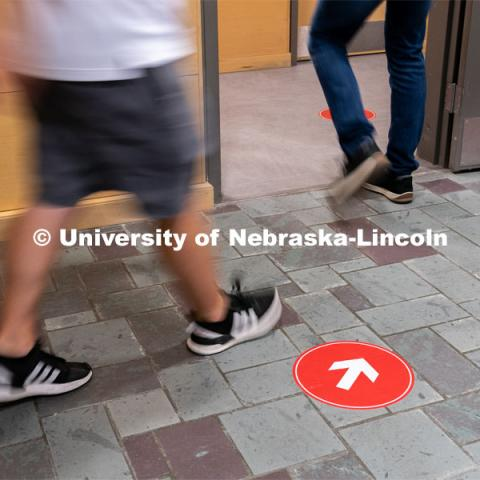 Directional floor arrows keep students at a safe distance. Students walk through the hallways inside of Andersen Hall to get to class during the first day of in-person instruction at the University of Nebraska-Lincoln on Monday, August 24, 2020. Photo by Jordan Opp for University Communication.