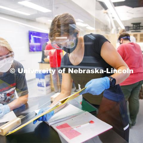 Johanna Ilves, right, and Clarissa Marron work on the report as the two lab partners are separated by an acrylic barrier in the Chemistry 105 lab. First day for in-person learning for the fall semester. August 24, 2020. Photo by Craig Chandler / University Communication.
