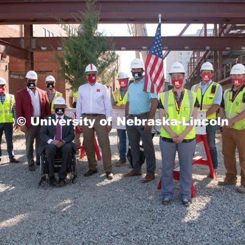 Left to right Joey Hausmann, Lance Perez, Chancellor Ronnie Green and Chad Wiles pose with the workers and the final beam. Due to COVID-19 precautions, a public ceremony was not able to be held. Instead, signatures from college and university supporters and others involved in the Phase I project were gathered either remotely or by signing the beam individually. The final beam was installed at the topping off ceremony for Engineering Project, August 26, 2020. Photo by Greg Nathan / University Communication.