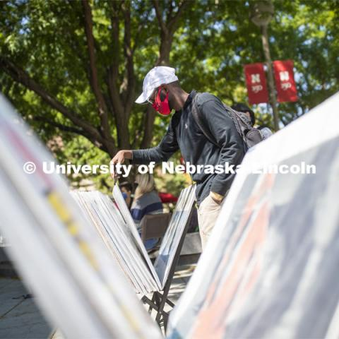 Mohamed Komi looks over posters for sale in front of the Nebraska Union Monday. City Campus. August 31, 2020. Photo by Craig Chandler / University Communication.