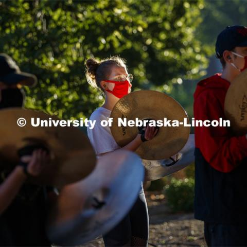 The sunrise reflects off of Skyler Krull's cymbal during the early morning practice. A sunrise serenade as the cymbals and bass line of the Cornhusker Marching Band practices outside Kimball Music Hall Tuesday morning, September 2, 2020. Photo by Craig Chandler / University Communication.