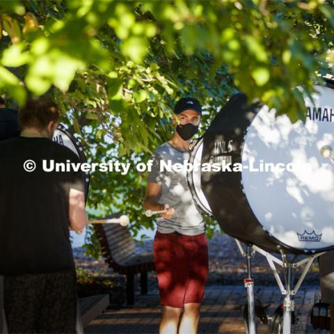 Carter Dawson directs the bass line practice under the trees outside the Lied Center. A sunrise serenade as the cymbals and bass line of the Cornhusker Marching Band practices outside Kimball Music Hall Tuesday morning, September 2, 2020. Photo by Craig Chandler / University Communication.
