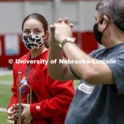 Audrey Fraser receives instruction from Tony Falcone, the Associate Director of Bands. Band members have used ingenuity to cover their horn's bell. One third of the marching band meets each morning at Cook to practice as the rest of the band practices in other locations where they can properly distance. Cornhusker Marching Band practice in Cook Pavilion. September 10, 2020. Photo by Craig Chandler / University Communication.