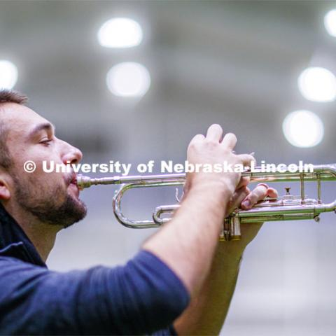 Nate Iverson plays his trumpet under the lights--of Cook Pavilion. One third of the marching band meets each morning at Cook to practice as the rest of the band practices in other locations where they can properly distance. Cornhusker Marching Band practice in Cook Pavilion. September 10, 2020. Photo by Craig Chandler / University Communication.