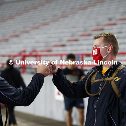 Midshipmen Christian New, left, and Chris Haidvogel fist bump after completing the run. UNL ROTC cadets and Lincoln first responders run the steps of Memorial Stadium to honor those who died on September 11. Each cadet ran more than 2,000 steps. September 11, 2020. Photo by Craig Chandler / University Communication.