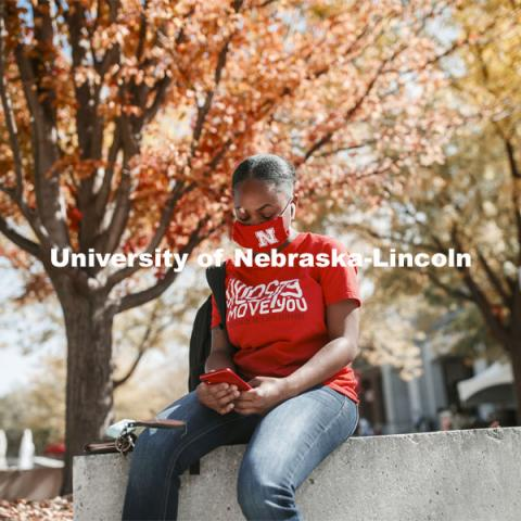 Brianna Rosalez, a freshman from Kansas City, enjoys the sunshine as she checks her phone during the noon hour outside the Nebraska Union. City Campus. October 7, 2020. Photo by Craig Chandler / University Communication.