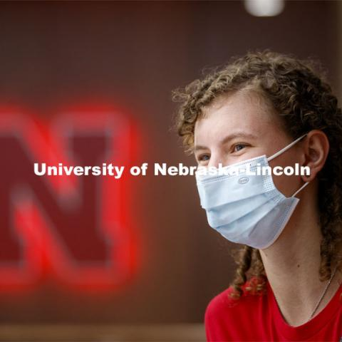 A young woman sits in front of a Nebraska N inside the remodeled Nebraska East Union. East Campus photo shoot. October 13, 2020. Photo by Craig Chandler / University Communication.