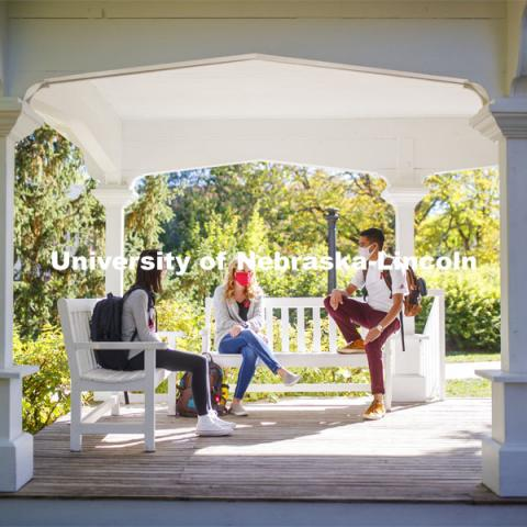 Tori Huffman, Sydney Brewer, and Sushant Timalsina enjoy the afternoon on Perin Porch on east campus. East Campus photo shoot. October 13, 2020.  Photo by Craig Chandler / University Communication