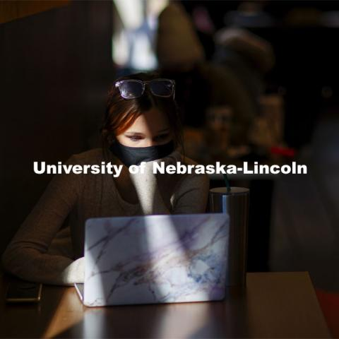 Emily Diesing, a sophomore from Omaha, studies in a ray of afternoon sunshine in the Nebraska Union. October 27, 2020. Photo by Craig Chandler / University Communication.