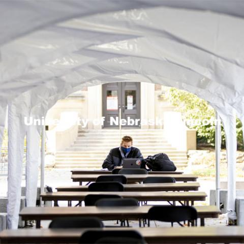 A young man studies in a tent outside. City Campus. October 28, 2020. Photo by Craig Chandler / University Communication.