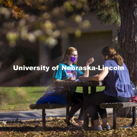 Madyson Hamling (dark blue top) and Emma Arthur study outside the Barkley Memorial Center on a warm November day. The two are speech pathology students. East Campus. November 6, 2020. Photo by Craig Chandler / University Communication.