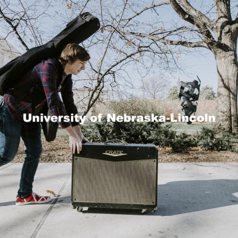 Brock Godown, a freshman from Geneva, rolls his amplifier back to his residence hall following a music class in Westbrook Music Building. November 16, 2020. Photo by Craig Chandler / University Communication.
