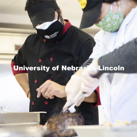 Professor Ajai Ammachathram oversees the carving of the prime rib as his Catering Management students prepare a wedding feast as the final project for the semester. November 18, 2020. Photo by Craig Chandler / University Communication.