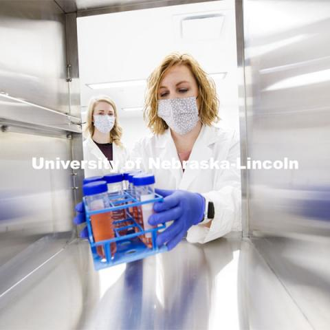 Kristin Beede, research manager with the Department of Food Science and Technology, passes bacterial cultures from the laboratory to the procedure room, where graduate student Ashley Toney awaits them. Nebraska Food for Health Center. November 19, 2020. Photo by Craig Chandler / University Communication.