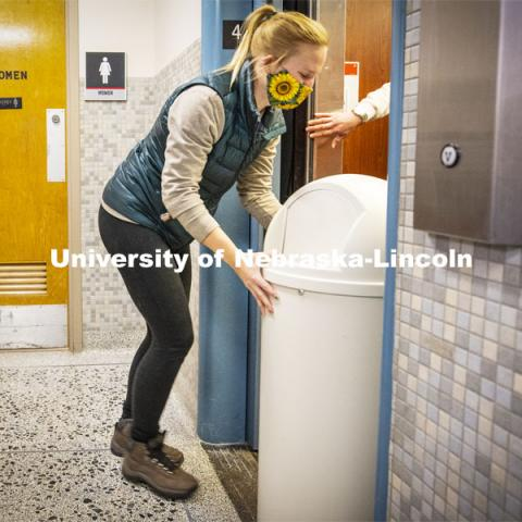 Anna Oetting, graduate students working in the Office of Sustainability, loads an old trashcan onto the Canfield Hall elevator so it can be hauled away. The Office of Sustainability is installing the new recycling stations in eight pilot buildings on all three campuses during break. December 1, 2020. Photo by Craig Chandler / University Communication.