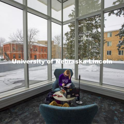 Lydia Cole, a senior from Plattsmouth, NE, studies in the corner seat ner the windows of the Dinsdale Family Learning Commons on East Campus. January 28, 2021. Photo by Craig Chandler / University Communication.