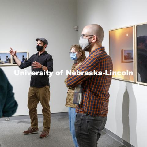 "Terry Ratzlaff discusses his MFA work ""Take Your Time"" to instructors and fellow masters students. In his work, Ratzlaff deconstructs and analyzes modern perceptions of time, chaos, order and obsession. In ""Take Your Time,"" he photographically deconstructs three idiosyncratic characters: a collector of model trains, an accumulator who makes annotations of train activities, and himself—a mimetic assemblage of collectors and accumulators. Each character is represented in its own collection of photographs that visually collide and collude with each other. By coupling each of the characters, Ratzlaff analyzes how obsession organizes a collection with the intent to control the experience of time. MFA Thesis Exhibitions in the Eisentrager•Howard Gallery in Richards Hall. April 2, 2021. Photo by Craig Chandler / University Communication."